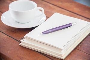 scrivania con un caffè e un taccuino foto
