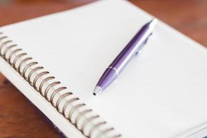 penna viola e un quaderno a spirale foto