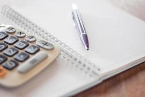 calcolatrice, penna e un taccuino foto