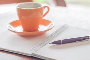 tazza di caffè, una penna e un taccuino su un tavolo di legno foto