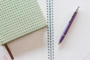 vista dall'alto di un taccuino verde, una penna e un taccuino a spirale foto