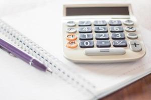 calcolatrice e una penna su un taccuino foto