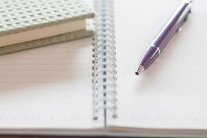 penna e un taccuino verde su un taccuino a spirale foto