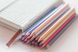 mucchio di matite colorate con un taccuino foto