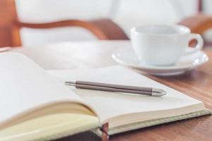 taccuino, penna e caffè su un tavolo foto