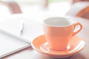 tazza di caffè arancione con una penna e un taccuino foto