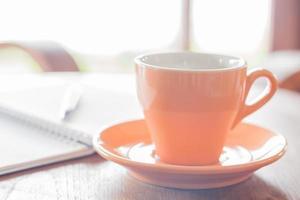 primo piano di una tazza di caffè arancione in una caffetteria foto
