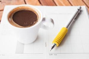 bianco tazza di caffè espresso su un notebook foto