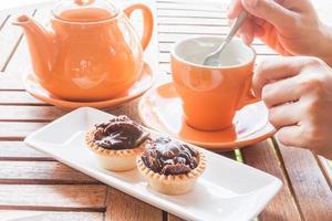 persona che mangia tè e cupcakes foto