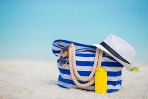 primo piano di una borsa e un cappello a strisce blu su una spiaggia