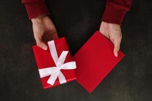 mani che tengono il mockup biglietto di auguri rosso