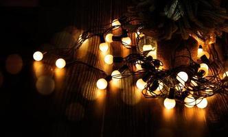 luci di natale e albero di natale su uno sfondo di legno