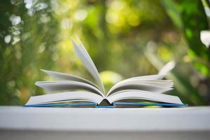 primo piano del libro aperto con sfondo bokeh di natura