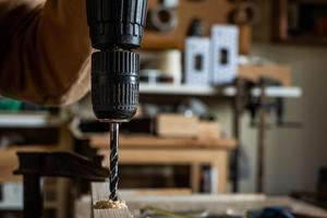 carpentiere che fa un trapano con una trottola su una tavola di legno foto