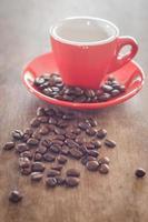 tazza di caffè rosso con chicchi di caffè su un tavolo di legno