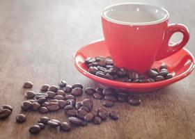 primo piano di una tazza di caffè rosso con chicchi di caffè su un tavolo di legno