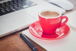 primo piano di una tazza rossa e di un laptop foto
