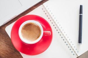 vista dall'alto di una tazza di caffè rossa e una penna su un taccuino foto