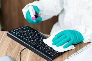 persona in tuta protettiva che pulisce la tastiera di un computer con spray