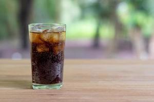 soda rinfrescante con ghiaccio in un bicchiere alto trasparente foto