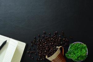scrivania nera con notebook e chicchi di caffè