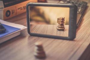 specchio con cornice nera sul tavolo di legno marrone