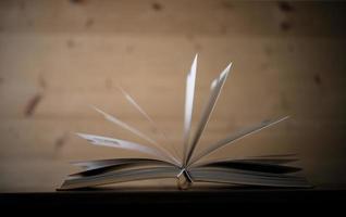 primo piano di un libro aperto su un tavolo di legno foto