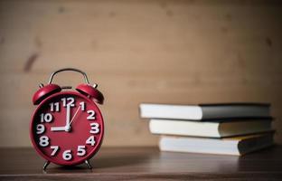 sveglia sulla tavola di legno con i libri