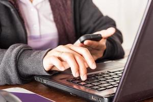 primo piano di una persona in possesso di un telefono durante la digitazione su un laptop foto