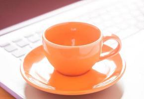 primo piano di una tazza di caffè su un computer portatile