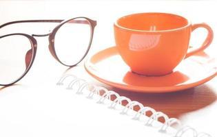 primo piano di una tazza di caffè e occhiali da vista