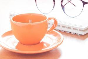 primo piano di una tazza di caffè arancione con gli occhiali