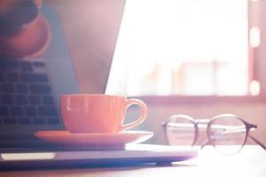 luce naturale su un laptop con una tazza di caffè e bicchieri foto