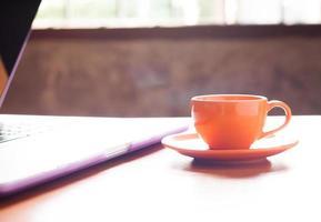 tazza di caffè accanto a un computer portatile foto