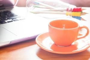 tazza di caffè accanto a un computer portatile su una scrivania foto