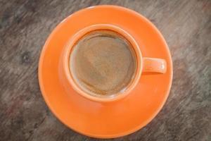vista dall'alto di una tazza di caffè arancione e piattino
