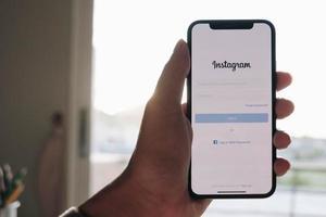 una donna tiene apple iphone x con applicazione instagram sullo schermo al caffè. instagram è un'app di condivisione di foto per smartphone.