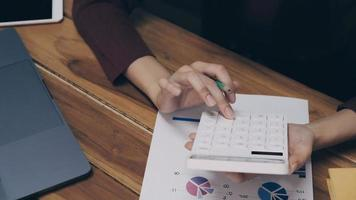 donna d'affari utilizzando calcolatrice e laptop alla scrivania in ufficio foto