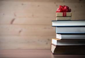 confezione regalo e libri sul tavolo di legno foto