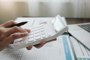 donna d'affari utilizzando una calcolatrice e laptop