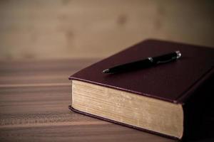prenota con una penna sul tavolo di legno foto