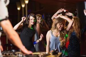 amici felici che ballano vicino allo stand del dj foto
