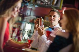 bel barman chiacchierando con i clienti foto