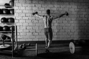 uomo di palestra in aumento manubri esagonali sollevamento pesi posteriore foto