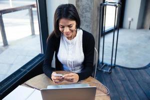 sorridente imprenditrice utilizza lo smartphone nella caffetteria foto