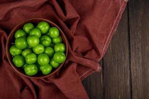 prugne verdi in una ciotola di legno scuro su sfondo rustico con spazio di copia