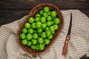 prugne verdi aspre in un cesto di vimini con un coltello da cucina su tessuto a quadri