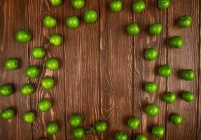 vista dall'alto di prugne verdi aspre sparse su uno sfondo di legno