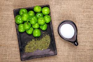 vista dall'alto di prugne verdi aspre con menta piperita essiccata su un vassoio nero su una tela di sacco
