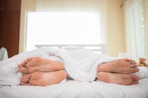 i piedi della coppia nel letto